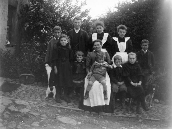 A family group of adults and children, posing in the garden of their house. The two young women in white aprons appear to be servants. There are two dogs, one of which presents its rear to the camera (left)