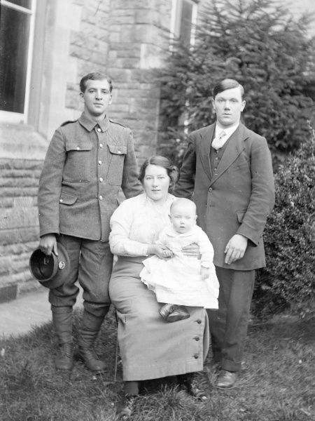 A family group photo in a garden, with a mother, her baby, and two men, one of them in uniform, during the First World War