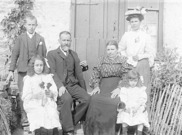 A family (parents, three children and grown-up daughter) pose for a group photograph in their garden, probably in the Mid Wales area. The two little girls are holding terrier puppies