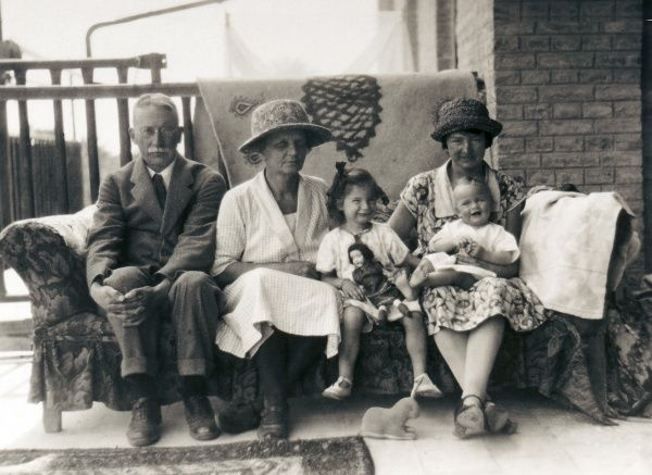A family group of two children, mother and grandparents, all sitting on a sofa on a verandah. The older girl holds a doll in her lap