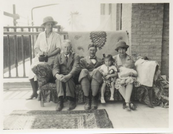 A family group of two children, mother, father and grandparents, all sitting on a sofa on a verandah. The grandmother is perching on the arm of the sofa. The older girl holds a doll in her lap, and is looking rather bored