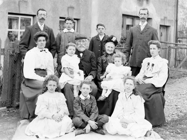 A family group of thirteen, covering three generations, with the grandparents in the middle -- three men, three women, three boys, two girls, and two toddlers