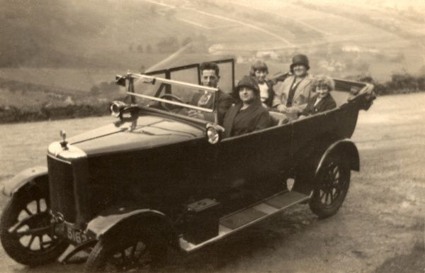 A family of five in a large open-top family car