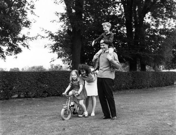 A family of four having fun in a park, the father gives his son a piggy back while the mother pushes her daughter on her bicycle. Date: 1970s