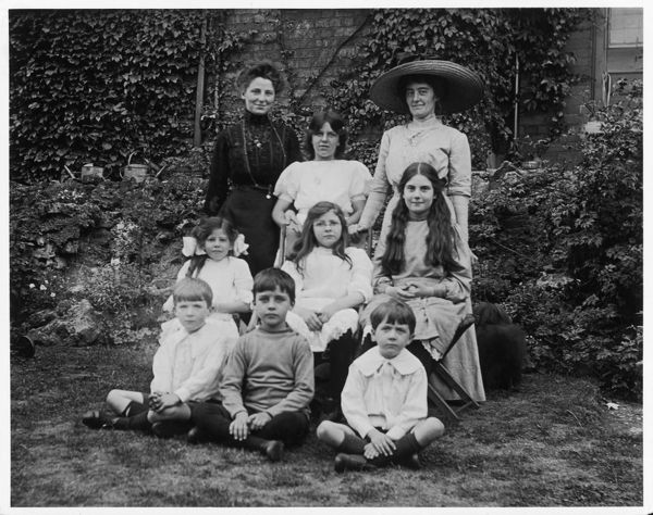 Mother and children, pose for the camera in the back garden. One of the younger girls wears spectacles. The boys wear knitted jerseys or shirts with large fall collars