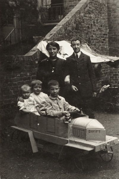 A late Victorian family pose in their backyard, the three children (of decreasing age) sit proudly in their fantastic homemade toy go-cart, entitled 'Swift&#39