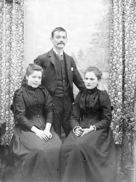 A family photo of a young man and two young women, possibly siblings