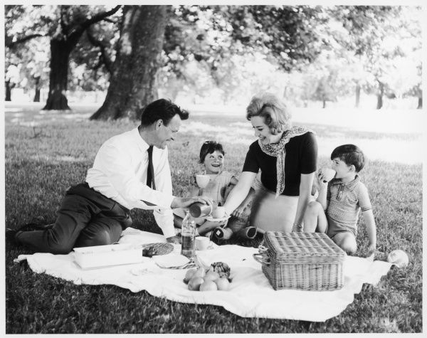 A young family enjoy a picnic together on a sunny day