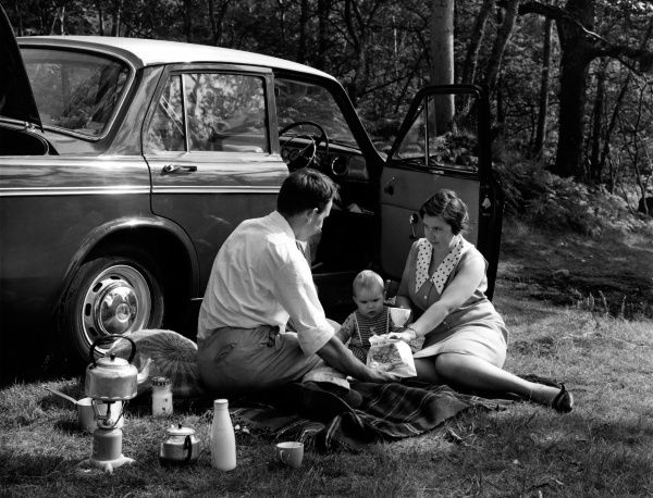 A family of three -- mother, father and baby -- enjoying a picnic in the woods by the side of their car