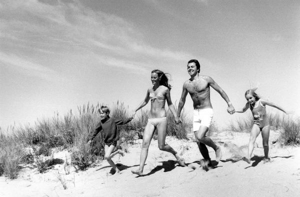 A family of four -- mother, father and two children -- running happily across the sand dunes on a beach in Cornwall