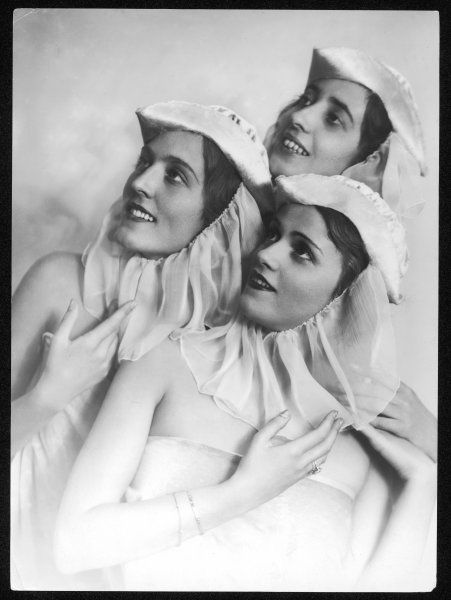 These three young women model the latest ideas for what to wear for a 'head-dress party' - very becoming tricorn hats! Made of panne velvet, with ninon veils under the chin