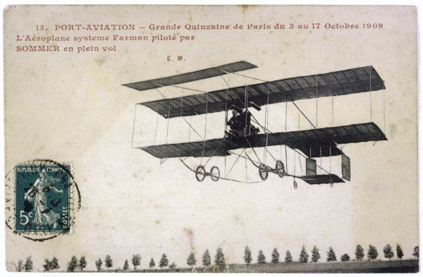At the 'Port D'Aviation', Paris, during the 'Grand Quinzaine' (fortnight) a Farman biplane is piloted by noted aviator Roger Sommer