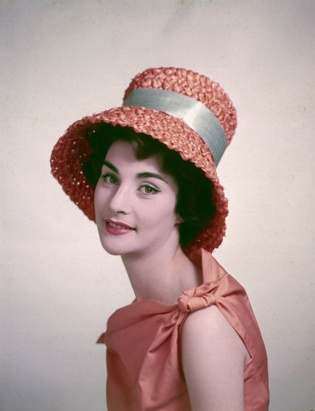 A young woman models a lovely orange basket hat. Date: circa 1960