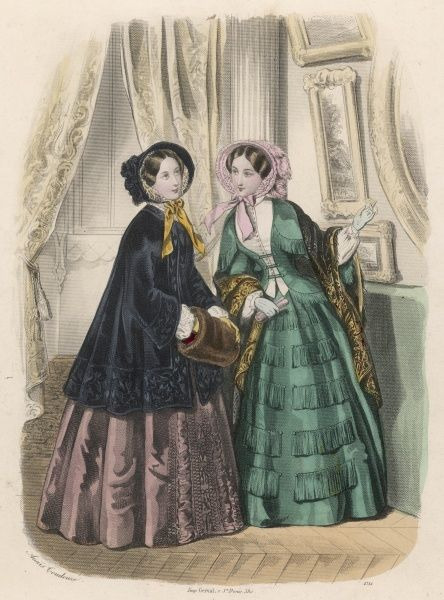 Green dress: waistcoat & open body with fringed basque & attached cape, skirt trimmed with fringing & a paisley shawl. Black mantle, brown fur muff & skirt with tablier trim