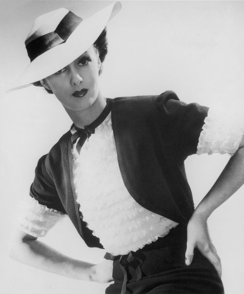 A female model wearing a rather unusual suit, with a ribbon choker and short- sleeved jacket with a rather fussy tiered blouse, topped off with a wide-brimmed hat