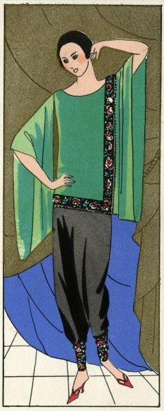 Fashionable young lady in a pyjama-style outfit by Molyneux, with black satin crepe trousers and a jade green crepe de chine top with wide sleeves. There is flowered edging on the tunic and at the ankles