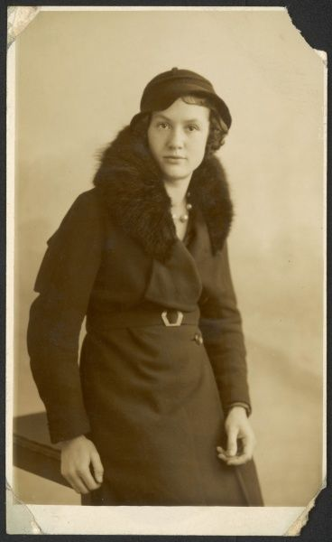 A fashionable young woman poses for her photo in a warm winter coat with a fur collar