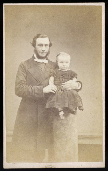 A man in a frock coat & light coloured necktie holds a very small child on a plinth who wears a short frock with short puffed sleeves, buttoned bodice & ankle strap shoes
