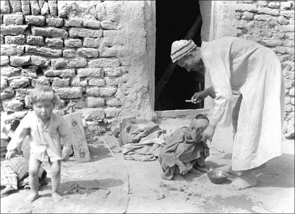 A father with two children outside their home in Kashgar, western China. He appears to be getting them washed from a small bowl of water. Photograph by Ralph Ponsonby Watts