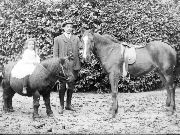 A father and daughter in a garden, probably somewhere in Mid Wales. He is standing next to a small horse, holding its bit, while she bravely sits on the back of a Shetland pony