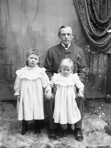 A father with his two young daughters, in the photographer's studio. There is a painted backdrop with a curtain draped at the side, and they are standing on a large furry rug