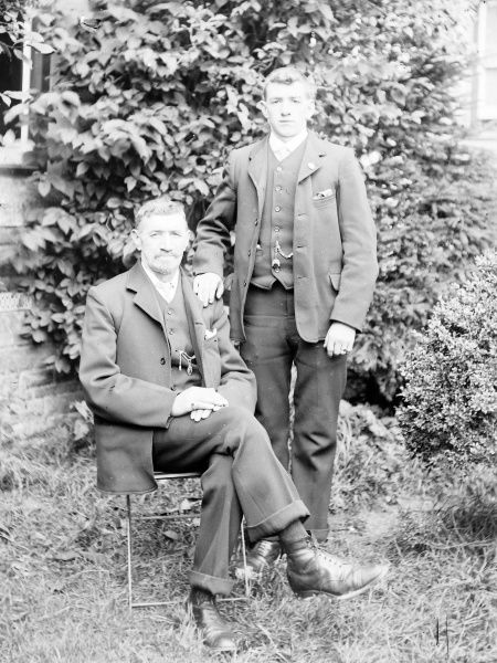 A father and son pose for their photograph in a garden, probably in the Mid Wales area. They are wearing very similar three-piece suits