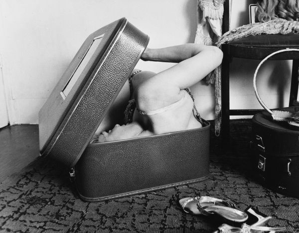 The female contortionist gets into a suitcase and pulls down the lid as she squeezes her shoulder in... Date: 1960s