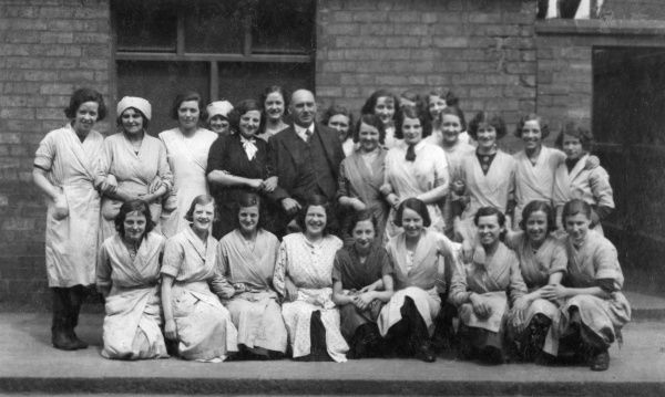 A group of female factory workers pose for a photo with their male boss at Burroughs & Sturgess, Frederick Street, Derby. Date: 1930s