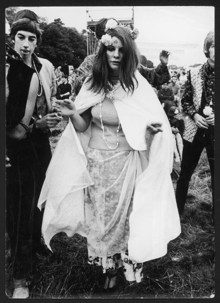 HIPPIES A spaced-out hippy woman, wearing the obligatory flowers in her hair, transfers, beads, tinsel and floaty layers of chiffon etc. Date: August 1967