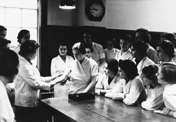 A new student is used in a medical demonstration by a senior student, in front of a class of female students at the Royal Free Hospital Medical School, London