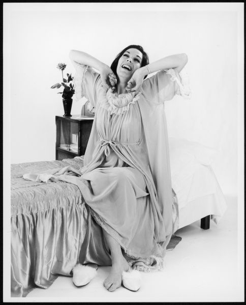 A woman sits on her bed in her night-gown having just woken up