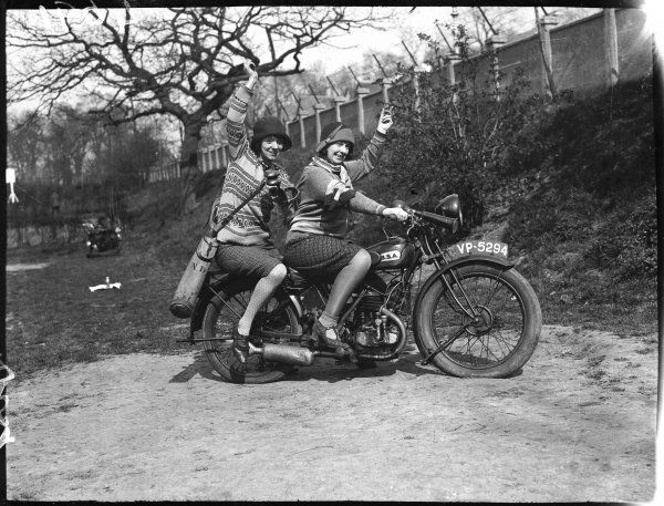 Two jolly young women motor cyclists, dressed rather impractically in knitwear and sensible skirts and without helmets are off for a round of golf with their clubs