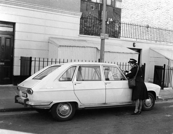 A female traffic warden in Chelsea, London, issuing a parking ticket to an unfortunate motorist. Date: late 1960s