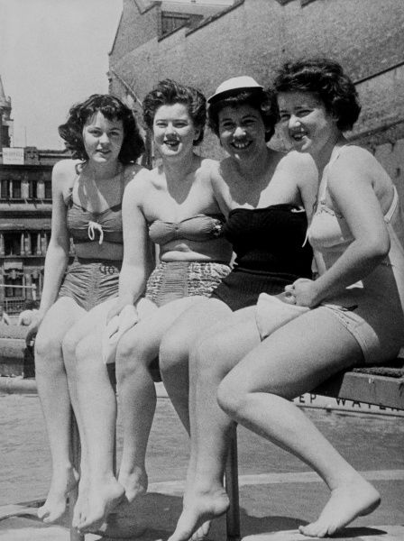 Four young women in swimwear: two in bikinis, two in one- piece costumes. Date: 1950s