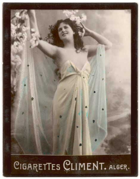 A young woman in semi- transparent dress raises her arms in a gesture of pleasure