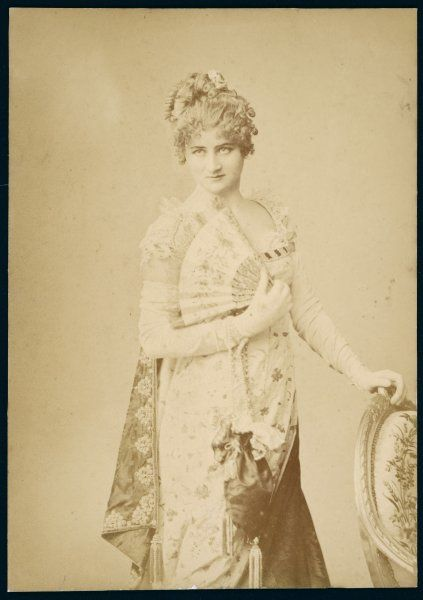 Demure Victorian woman posing with a fan