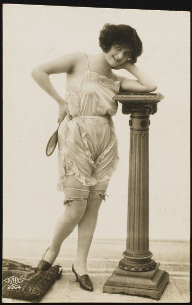 A smiling young Frenchwoman in her frilly underwear leans on a classical pillar in the photographer's studio