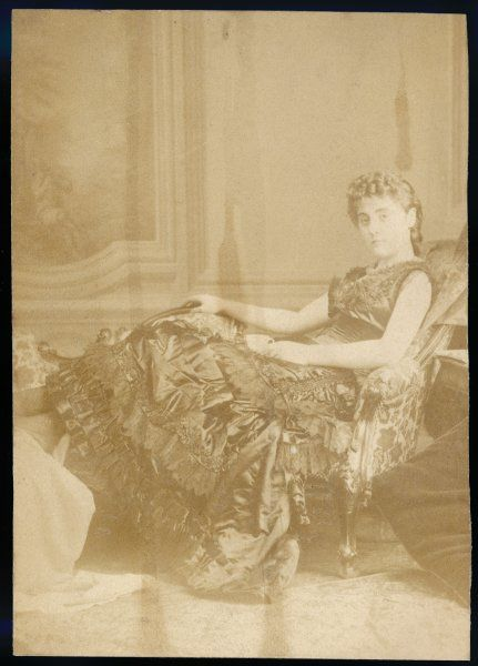 An elegant Victorian woman reclining on a chaise longue