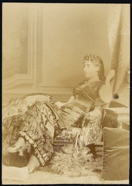 An elegant Victorian woman relaxing on a chaise longue