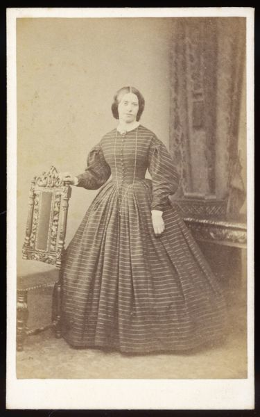 A dress in a horizontally striped fabric with front buttoning bodice, gigot sleeves, white cuffs & collar, a plain skirt, brooch & pendant on a long chain