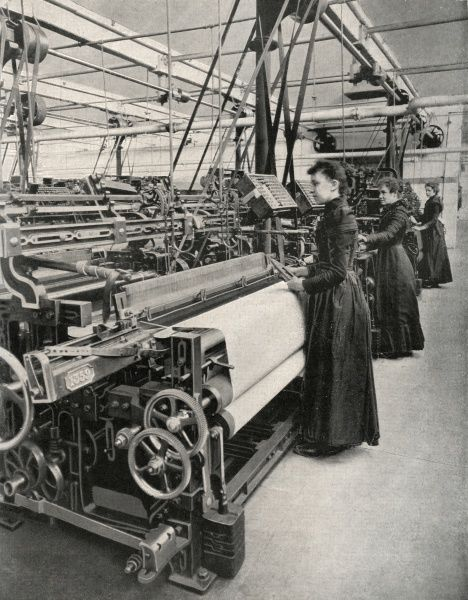 Female wool weaving operators tend their machines at a Yorkshire factory