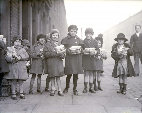 Poor working class children in London's East End, queueing up for the 'Fern Street Settlement': Children with their bundles of toys, which cost them a farthing each. Date: early 1930s