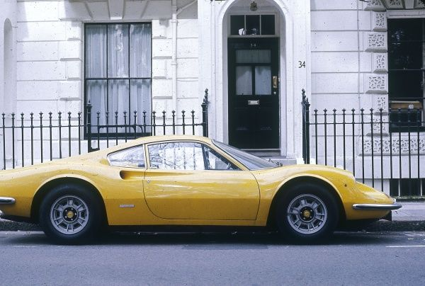 A bright yellow Ferrari Dino, parked outside a smart period property. Date: 1974