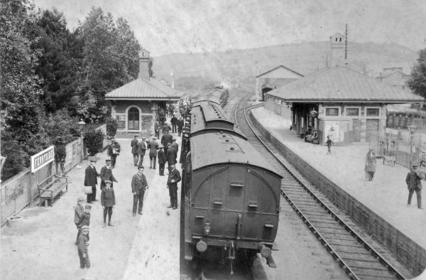 View of Ferryside Railway Station on the Great Western Railway, Carmarthenshire, South Wales. Probably taken from the footbridge across the tracks. A train stands at the left-hand platform, and passengers are in the process of getting on and off