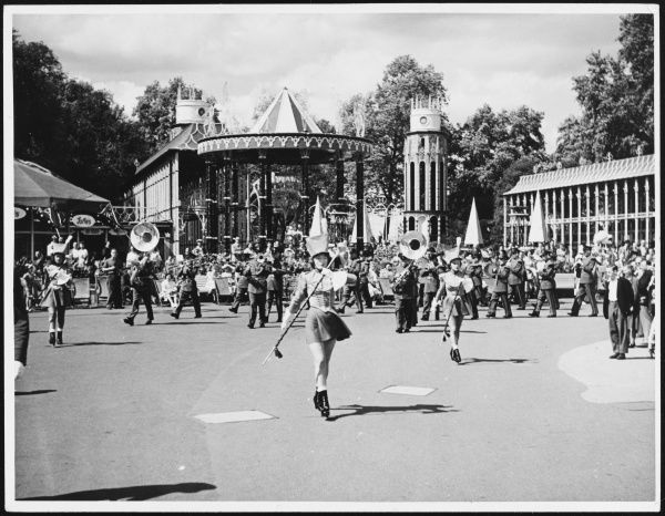 Majorettes in short skirts twirl their batons, followed by a marching brass band, at the Festival Pleasure Gardens, Battersea, Festival of Britain celebrations