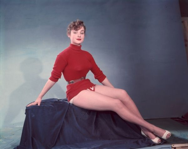 Epitomising the 1950s sweater girl, this model poses wearing a red jumper, cinched at the waist with a belt, with lipstick to match