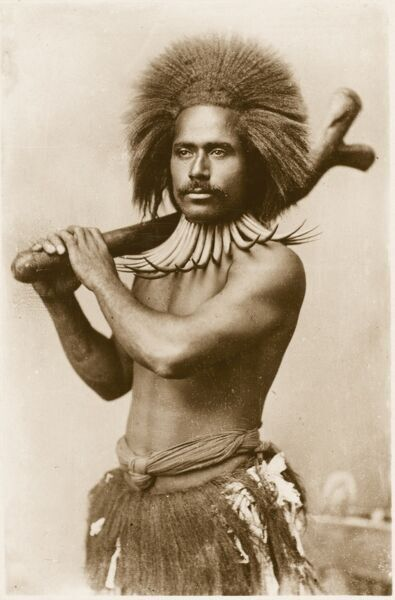 A Fijian Man with war club resting on his shoulder. He wears a spectacluar neckace of carved bones and wears his hair brushed upwards in a wild and alarming fan-shape