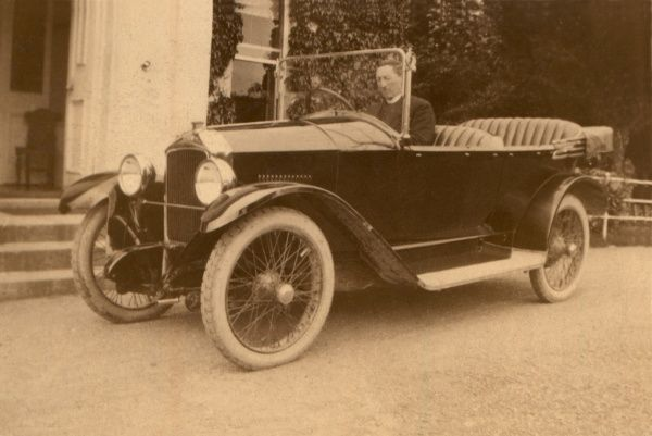 A gentleman in his fine tourer outside his country seat