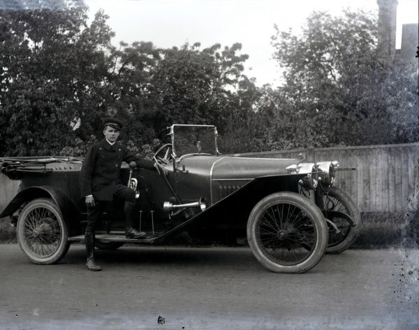 A young Gent standing, one foot on the running board, alongside his fine large tourer