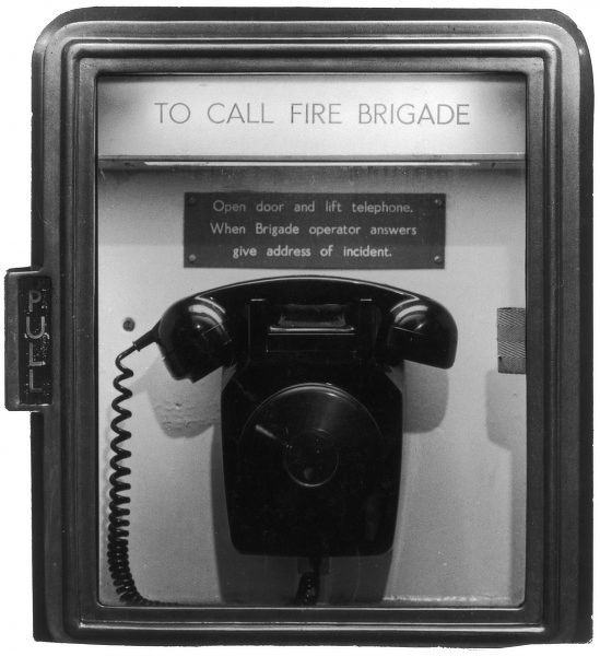 An emergency telephone for contacting the fire brigade, housed in a glass case. Photograph by Heinz Zinram